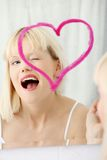Young beautiful woman drawing big heart on mirror. Royalty Free Stock Photography
