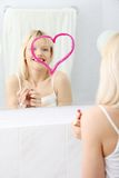 Young beautiful woman drawing big heart on mirror. Stock Photo