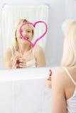 Young beautiful woman drawing big heart on mirror. stock photo