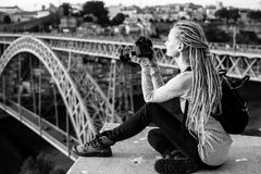 Young beautiful woman with dreadlocks and a camera sits taking pictures of a Dom Luis I bridge  in old Porto, Portugal. Royalty Free Stock Photos
