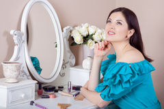 Young beautiful woman with dress apply makeup. Stock Image