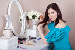 Young beautiful woman with dress apply makeup. Royalty Free Stock Image