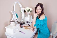 Young beautiful woman with dress apply makeup. Stock Photos