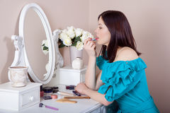 Young beautiful woman with dress apply makeup. Royalty Free Stock Images