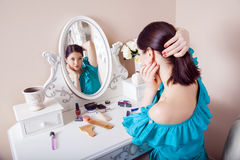 Young beautiful woman with dress apply makeup. Stock Images