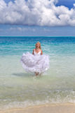 Young beautiful woman in a dress of the bride runs on waves of the sea Stock Photo