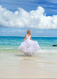 Young beautiful woman in a dress of the bride runs on waves of the sea Royalty Free Stock Photo