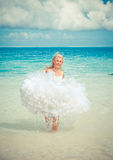 Young beautiful woman in a dress of the bride runs on waves of the sea,with a retro effect. The young beautiful woman in a dress of the bride runs on waves of Royalty Free Stock Image