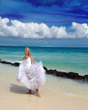 Young beautiful woman in a dress of the bride. The young beautiful woman in a dress of the bride standing at sea edge Stock Photography