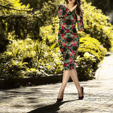 Young beautiful woman in a dress and shoes goes on Green Street. Close-up Royalty Free Stock Photography