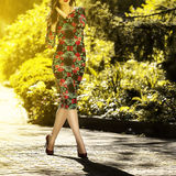 Young beautiful woman in a dress and shoes goes on Green Street. Close-up Stock Images