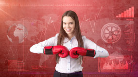 Young beautiful woman dress in suit standing in combat pose with red boxing gloves. Business concept. Royalty Free Stock Photo
