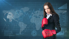 Young beautiful woman dress in suit standing in combat pose with red boxing gloves. Business concept. Royalty Free Stock Images