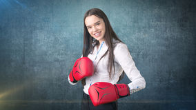 Young beautiful woman dress in white shirt standing in combat pose with red boxing gloves. Business concept. Stock Photos