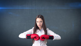 Young beautiful woman dress in white shirt standing in combat pose with red boxing gloves. Business concept. Royalty Free Stock Photography