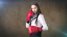 Young beautiful woman dress in white shirt standing in combat pose with red boxing gloves. Business concept. Stock Photo