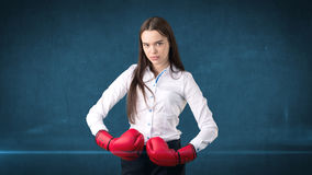 Young beautiful woman dress in white shirt standing in combat pose with red boxing gloves. Business concept. Stock Photography
