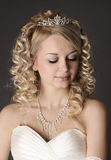 Young woman dressed as a bride on a gray. Royalty Free Stock Photography
