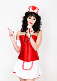 Young beautiful woman dressed as nurse, medical carnival costume, she holding a stethoscope Royalty Free Stock Image