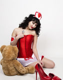 Young beautiful woman dressed as nurse, medical carnival costume, she holding a stethoscope and sitting on a floor with Stock Photos