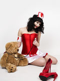 Young beautiful woman dressed as nurse, medical carnival costume, she holding a stethoscope and sitting on a floor with Stock Images