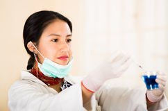 Young beautiful woman dressed in doctors coat and red necklace, facial mask pulled down to chin, holding up blue Stock Photography