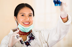 Young beautiful woman dressed in doctors coat and red necklace, facial mask pulled down to chin, holding up blue Stock Images
