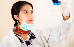 Young beautiful woman dressed in doctors coat and red necklace, facial mask pulled down to chin, holding up blue Royalty Free Stock Photography