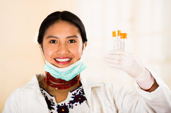 Young beautiful woman dressed in doctors coat and red necklace, facial mask pulled down to chin, holding up syringes Royalty Free Stock Photos