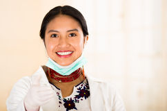 Young beautiful woman dressed in doctors coat and red necklace, facial mask pulled down to chin, smiling happily, egg Royalty Free Stock Image