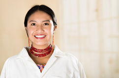 Young beautiful woman dressed in doctors coat and red necklace looking into camera smiling, egg white clinic background Stock Image