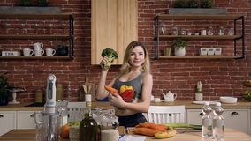 Young beautiful woman dressed in sport suit standing behind kitchen table with fresh broccoli in the hand, holding glass stock video footage