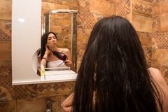 Young, beautiful woman dries hair in the bathroom with a hair dryer royalty free stock photo