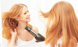 Young beautiful woman dries and style your hair dryer. At home in front of a mirror stock images
