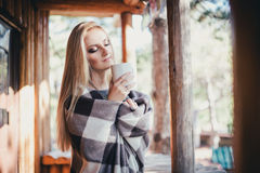 Young beautiful woman drinking cocoa in a wooden coutry house Royalty Free Stock Photo