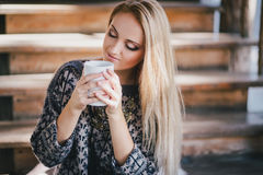 Young beautiful woman drinking cocoa in a wooden coutry house Stock Photo
