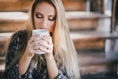 Young beautiful woman drinking cocoa in a wooden coutry house Stock Photography