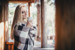 Young beautiful woman drinking cocoa in a wooden coutry house Royalty Free Stock Images