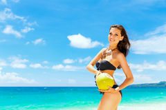 Young beautiful woman , drinking coconut water on tropical beach Stock Image