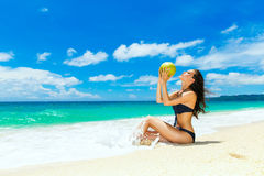 Young beautiful woman , drinking coconut water on tropical beach Stock Photography