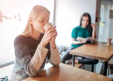 Young beautiful woman drinking coffee at cafe bar. Female model in the morning at restaurant. Young beautiful women drinking coffee at cafe bar. Female model in Stock Photos