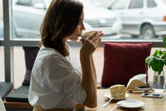 A young beautiful woman drinking coffee in a cafe. young woman in business clothes on a lunch break Royalty Free Stock Photography