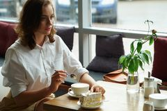 A young beautiful woman drinking coffee in a cafe. young woman in business clothes on a lunch break Stock Photo