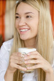 A young beautiful woman is drinking from a cup Royalty Free Stock Images