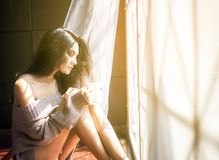 Young beautiful woman drinking cup of coffee sitting home by the window.  royalty free stock images