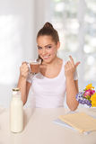 Young beautiful woman drinking a glass of hot drink while making Royalty Free Stock Image