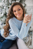 Young beautiful woman drinking hot coffee sitting on the couch i Royalty Free Stock Photography