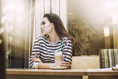Young beautiful woman drinking latte in the coffee shop at a tab Stock Photos