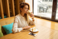 Young beautiful woman drinking latte in coffeeshop Royalty Free Stock Photos