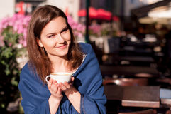 Young beautiful woman drinking morning coffee in an outdoor cafe Stock Photos
